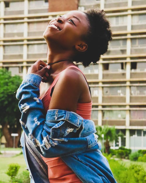 Side view of black woman in denim jacket smiling while standing in city near multi storey building during summer day