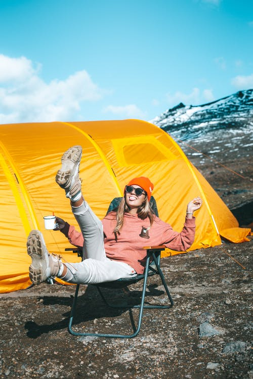 Happy female sitting on chair near tent on mountain slope
