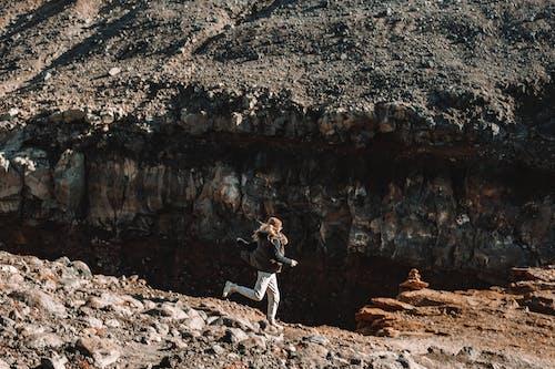 Woman running on desert rocky terrain