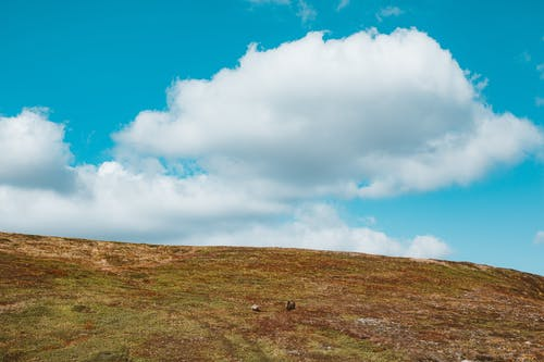 Landscape of hill slope with clouds above