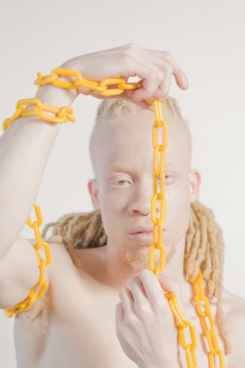 Topless Man Holding Yellow Chain