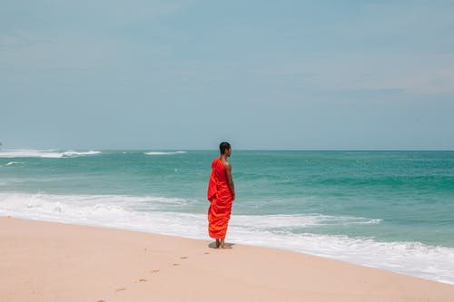 Unrecognizable Asian man in traditional orange cloth on beach