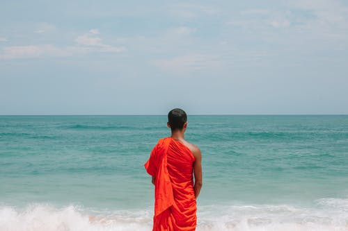 Unrecognizable Asian male monk in traditional orange robe on seashore
