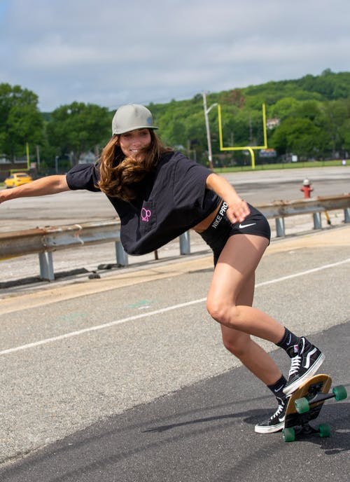 Full body of female with long hair in sportswear and hat riding skateboard on asphalt road near green trees in city