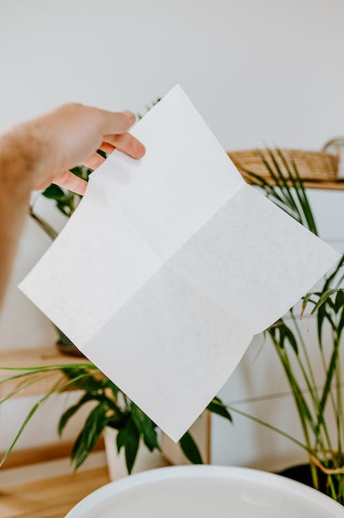 Crop man with blank paper sheet in apartment