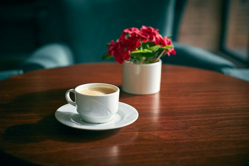 From above of ceramic cup of coffee on saucer near small vase with bright artificial flowers on wooden table at home