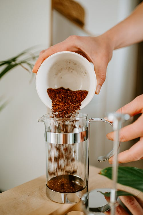 Crop woman pouring coffee into French press