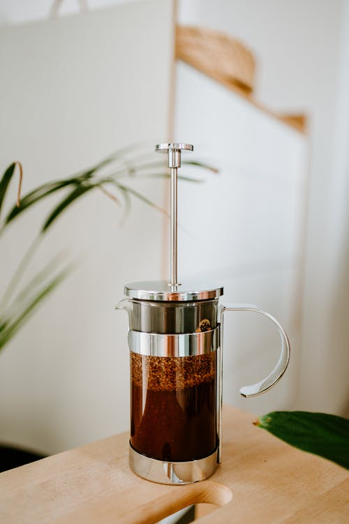 Contemporary French press with fresh coffee on table