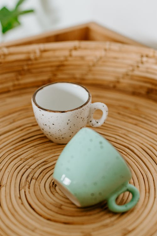 Ceramic cups with spots on wicker surface