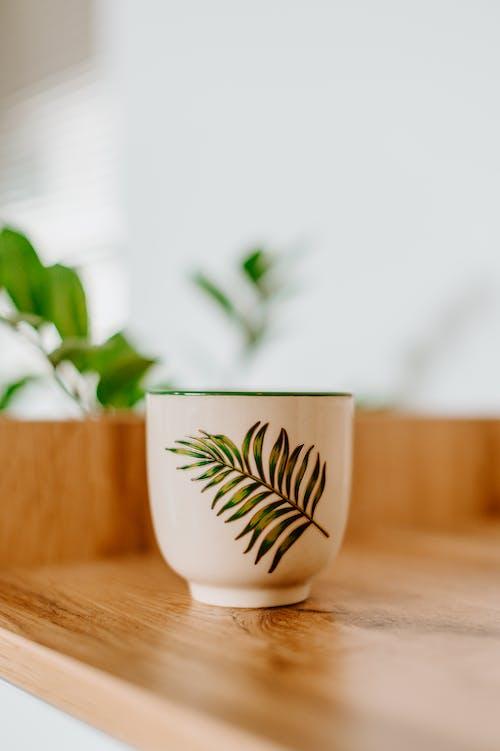 Ceramic cup with original leaf ornament on shelf