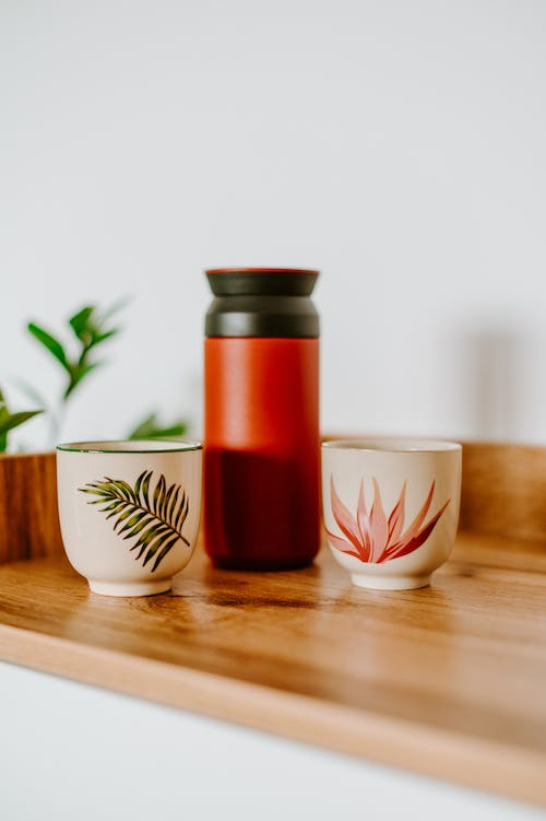 Bright thermos between creative design cups on shelf