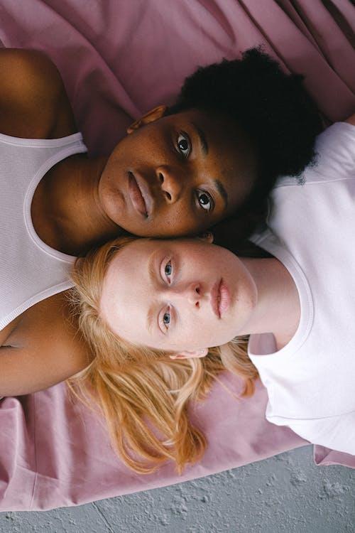 Interracial Women Lying Head to Head in Opposite Direction