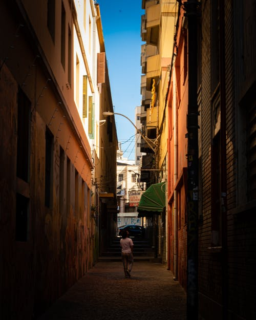 Anonymous tourist walking on narrow street in city old district