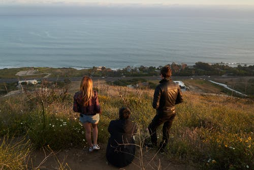 Group of unrecognizable people admiring seascape from high hill in countryside