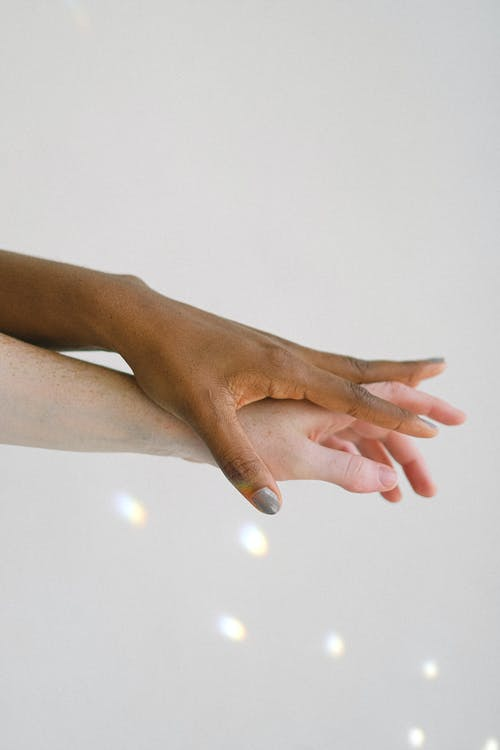 Interracial Peoples Hands on Top of Another