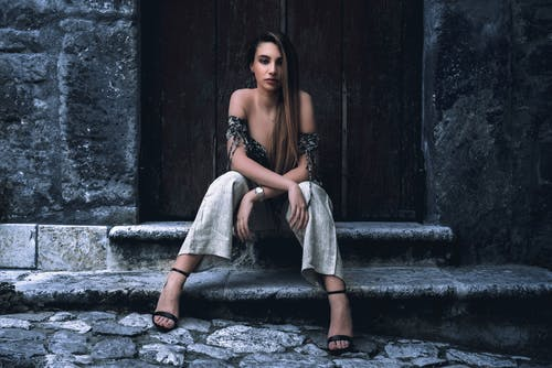 Full body of young gorgeous female model with long hair in stylish outfit sitting on stone steps near shabby wooden door and looking away