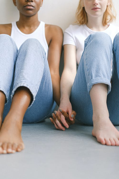 Women Sitting on Floor and Holding Hands
