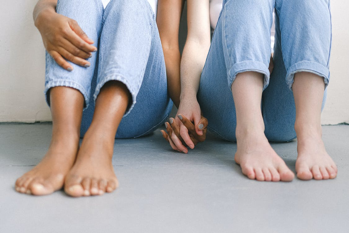 Женщины сидят на полу и держатся за руки