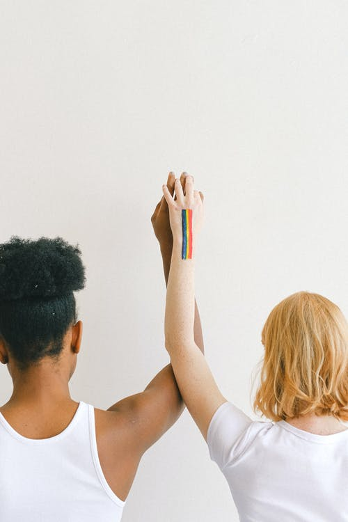 Women With Arms Raised and Holding Hands