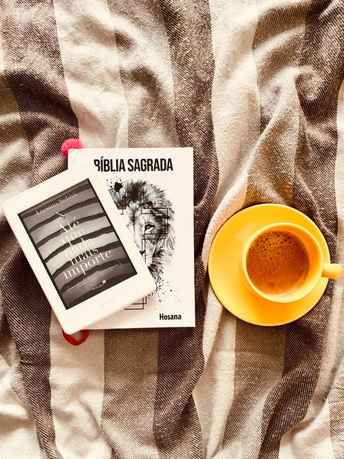Cup of coffee arranged on bed with books