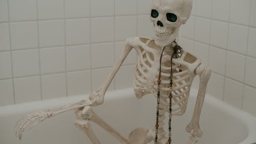 White skeleton with long chaplet sitting in bath without water in bathroom with white tiles on wall