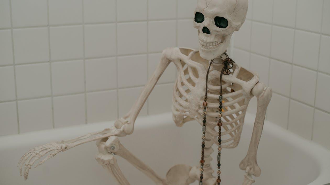 Human skeleton sitting in bathtub without water