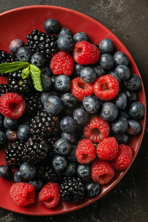 Bowl with assorted fresh berries on table