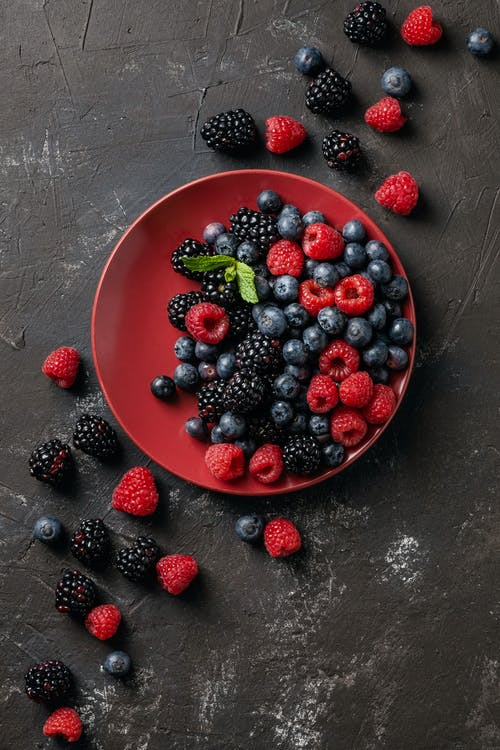 Top view of delicious blackberries and raspberries with blueberries on red round plate with more berries scattered around on dark grungy surface