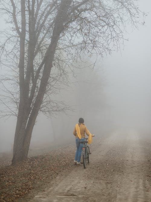 Anonymous woman with bicycle in foggy countryside