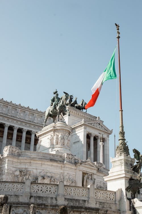 Majestic classical monument with waving flag nearby