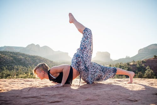 Woman doing One Legged Chin Stand in nature