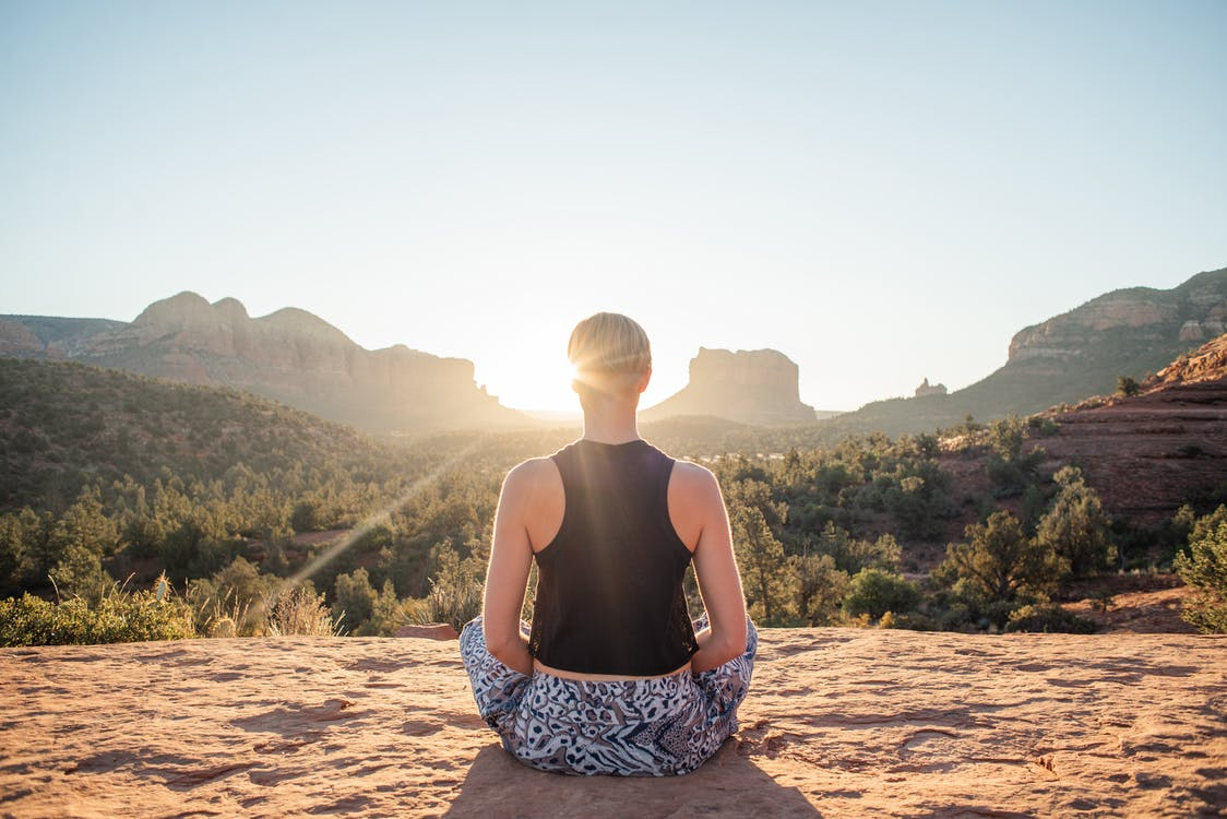 Back view of anonymous fit woman in comfortable summer wear sitting in Padmasana and meditating on sunlit cliff at sunrise