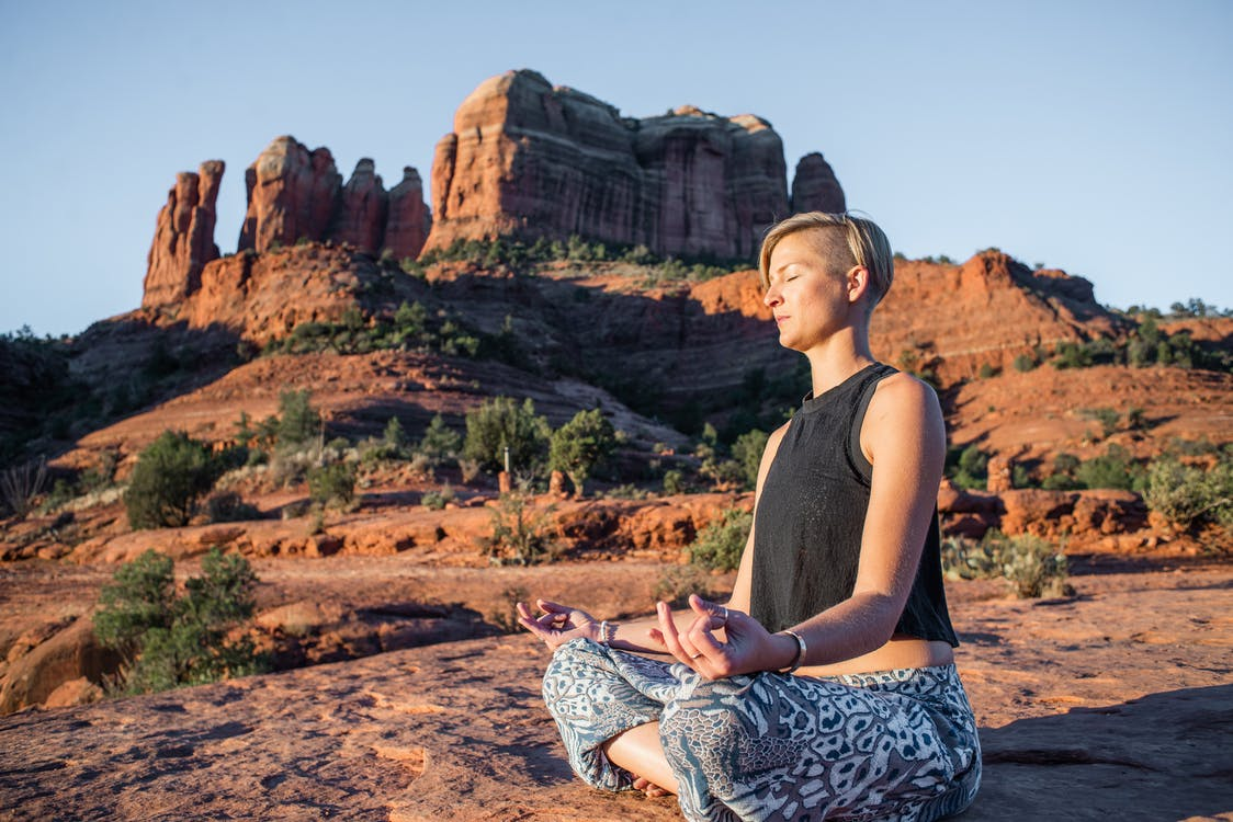 Calm lady meditating while sitting in Padmasana on rocky terrain