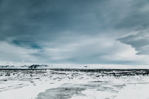 Picturesque scenery of wild peaceful terrain in highland covered with snow against cloudy sky in winter