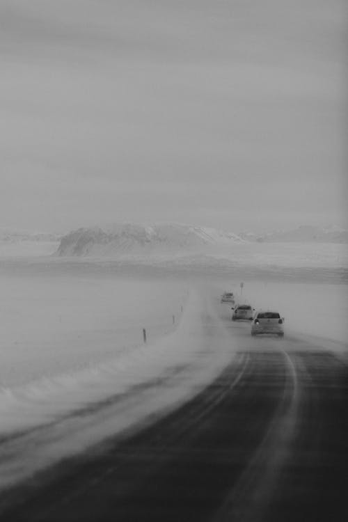 SUV cars riding on asphalt road surrounded by snowy terrain against gloomy cloudy sky in winter
