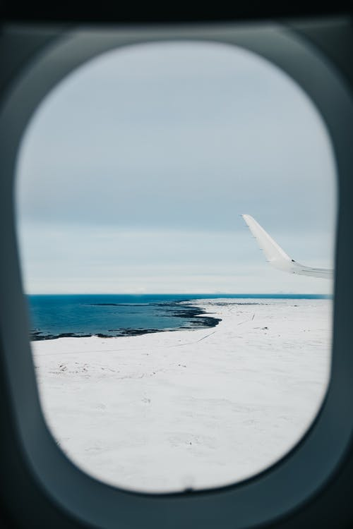 Through window wing of plane on airfield surrounded by snowy terrain near blue ocean on overcast day