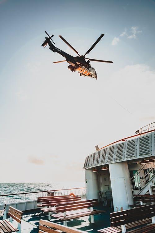 From below of bottom part of modern helicopter with spinning rotor blades above wooden benches on cruise ship in high ocean