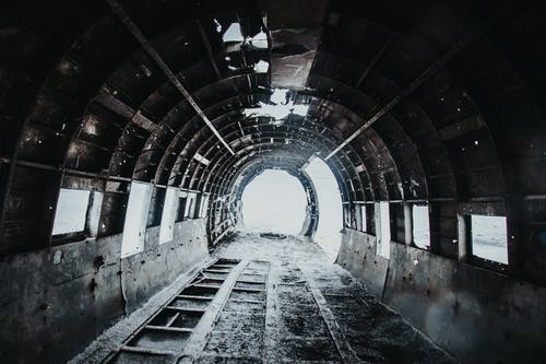 Interior of desolated old empty destructed airplane with dirty floor covered with snow and holes on walls and ceiling