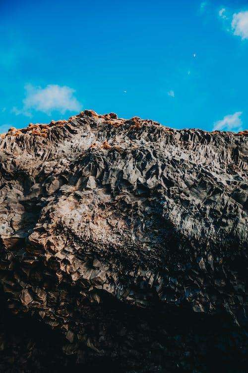 Blue sky over bare cliff