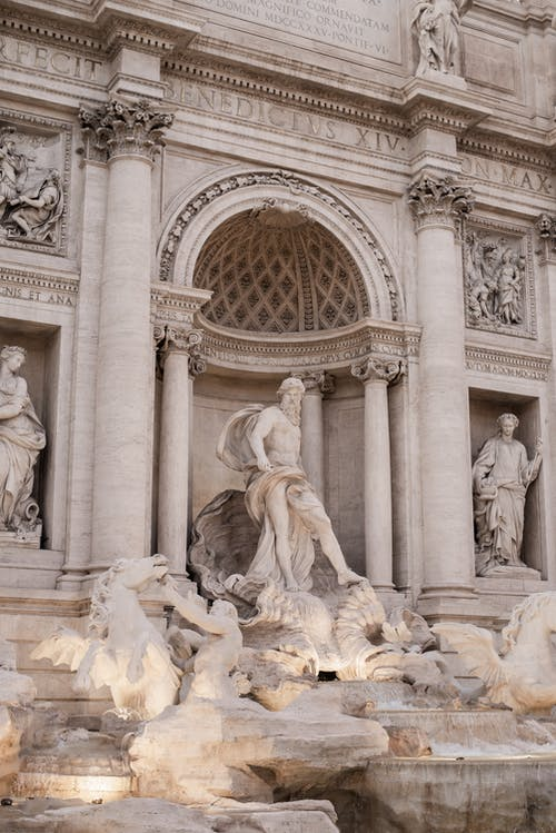 Statue of Oceanus at magnificent Baroque Trevi Fountain made of travertine stone in Rome