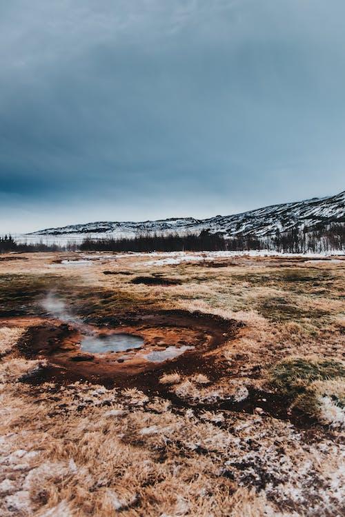 Volcanic terrain with geyser in snowy valley