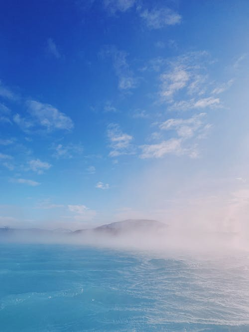 Azure ocean located near green hills covered with mist against blue sky in sunny day on mountainous terrain near seascape