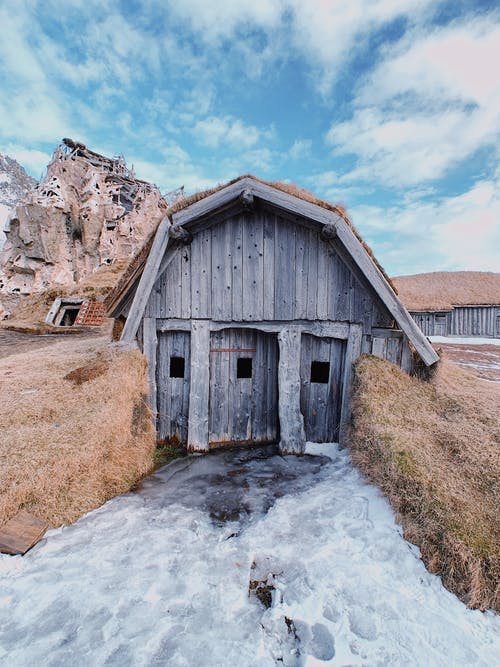 Shabby wooden structure located in ravine on snowy ground near rocky cliff against cloudy sky in countryside in spring time