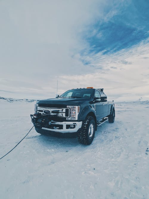 Modern black vehicle driving on trailer on snowy ground against cloudy sky in winter time in daylight in cold weather