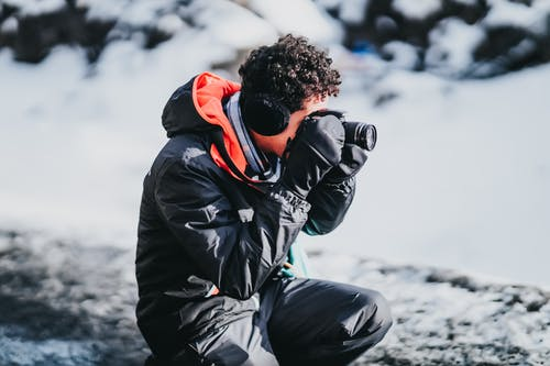 Side view of male photographer with curly hair in gloves squatting near snowy ground while taking pictures on camera of frozen scenery