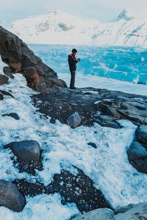 Unrecognizable man with photo camera in snowy hillisde