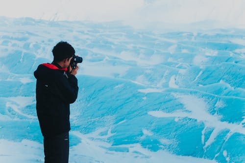 Man taking photo of snowy mountainous terrain