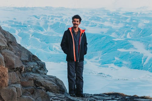 Full body cheerful man in winter outerwear smiling at camera while standing on rocky range in snowy valley