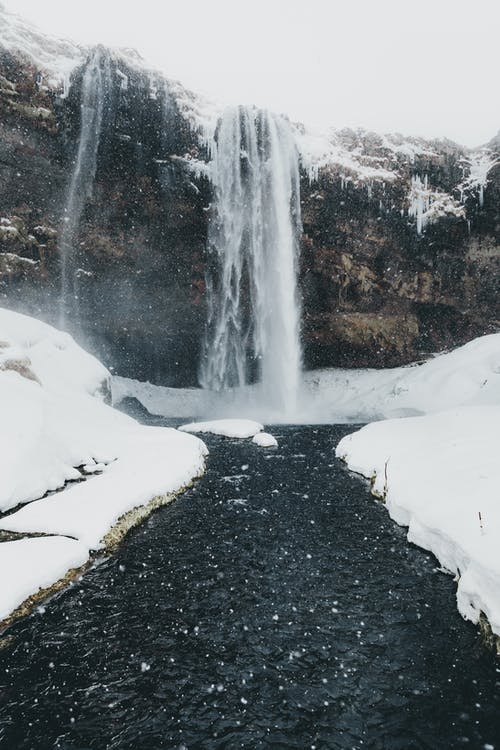 Falling snow above cold rough river and majestic waterfall on high rocky cliff