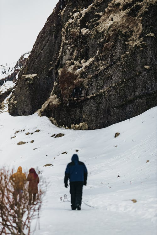 Back view of people strolling at bottom of high rocky mountain while exploring Nordic nature